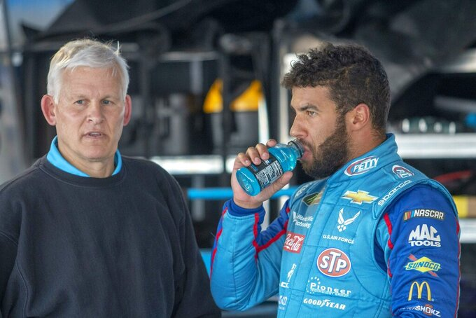 Bubba Wallace talks with a crew member during practice for the NASCAR Monster Energy Cup Series race at Martinsville Speedway in Martinsville, Va., Saturday, March 23, 2019. (AP Photo/Matt Bell)