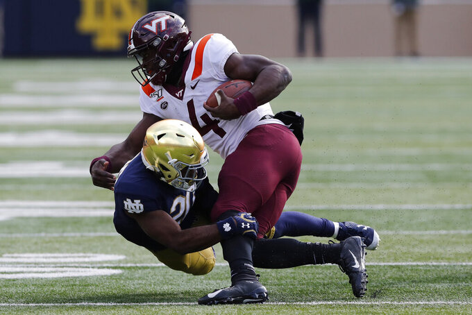 Virginia Tech quarterback Quincy Patterson II (4) is tackled by Notre Dame cornerback Shaun Crawford (20) during the first half of an NCAA college football game, Saturday, Nov. 2, 2019, in South Bend, Ind. (AP Photo/Carlos Osorio)