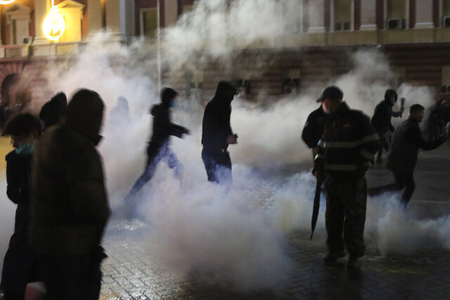 Protester walk among smoke by tear gas during clashes outside the Prime's Minister office in Tirana, Albania , on Wednesday, Dec. 9, 2020. Clashes have broken out in Tirana during a protest by hundreds of Albanians demanding the interior minister's resignation over the fatal police shooting of a 25-year-old man who had breached a coronavirus-linked curfew. (AP Photo/Hektor Pustina)
