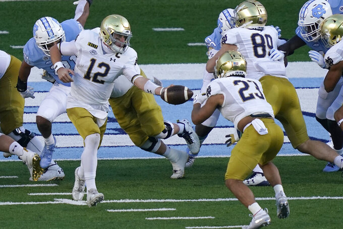 Notre Dame quarterback Ian Book (12) hands off to running back Kyren Williams (23) during the first half of an NCAA college football game against North Carolina in Chapel Hill, N.C., Friday, Nov. 27, 2020. Book scored a touchdown on the play. (AP Photo/Gerry Broome)