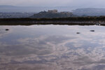 The sky is reflected in a puddle on Lycabettus hill as in the background is seen the city of Athens with the ancient Acropolis hill after a rainstorm, on Wednesday, April 17, 2019.  A lightning bolt struck the Acropolis in Athens during a rainstorm Wednesday, lightly injuring two visitors and two guards but causing no damage to the country's most famous ancient site, Greek officials said.(AP Photo/Petros Giannakouris)