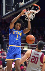 UCLA center Moses Brown (1) dunks next to Stanford center Josh Sharma (20) during the first half of an NCAA college basketball game Saturday, Feb. 16, 2019, in Stanford, Calif. (AP Photo/Tony Avelar)