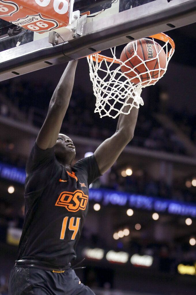 Oklahoma State's Yor Anei dunks during the first half of an NCAA college basketball game against TCU in the Big 12 men's tournament Wednesday, March 13, 2019, in Kansas City, Mo. (AP Photo/Charlie Riedel)