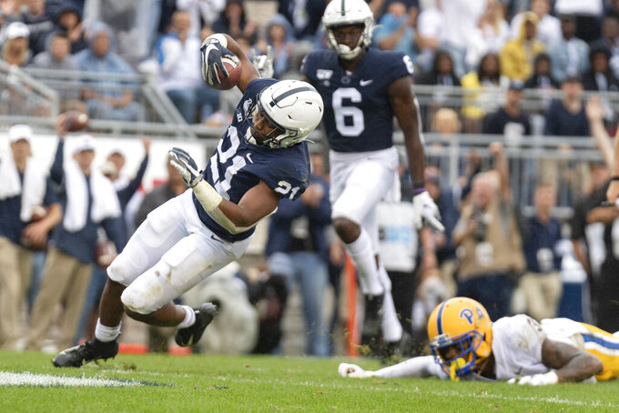 Penn State running back Noah Cain (21) eludes Pittsburgh defensive back Damar Hamlin (3) on his way to score on a 13-yard touchdown run in the third quarter of an NCAA college football game in State College, Pa., on Saturday, Sept. 14, 2019. Penn State defeated Pittsburgh 17-10. (AP Photo/Barry Reeger)