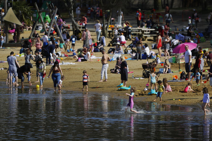 People enjoy the warm weather at Ruislip Lido in London, Tuesday, March 30, 2021. Temperatures in parts of the UK are expected to be significantly warmer this week as families and friends are reunited and outdoor sporting activities are allowed to resume in England. (AP Photo/Kirsty Wigglesworth)