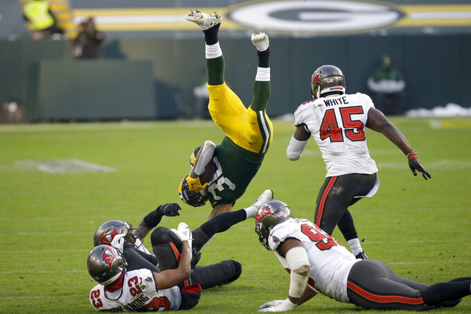 Green Bay Packers' Jamaal Williams (30) is upended by the Tampa Bay Buccaneers during the second half of the NFC championship NFL football game in Green Bay, Wis., Sunday, Jan. 24, 2021. (AP Photo/Mike Roemer)