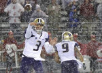 Washington quarterback Jake Browning (3) passes as running back Myles Gaskin (9) runs past him during the second half of an NCAA college football game, Friday, Nov. 23, 2018, in Pullman, Wash. (AP Photo/Ted S. Warren)