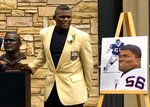 FILE - In this Aug. 7, 1999, file photo, former New York Giants' Lawrence Taylor poses with his portrait and bust during enshrinement ceremonies at the Pro Football Hall of Fame in Canton, Ohio. L.T. was the No. 2 overall pick in 1981 behind South Carolina RB George Rogers. In 13 seasons, he transformed the game, his position and the Giants, leading them to two Super Bowls. Taylor left as the NFL's No. 2 sacks leader. (AP Photo/Mark Duncan, File)