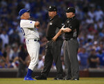 Chicago Cubs manager Joe Maddon left, argues with umpires Sam Holbrook middle, and Sean Barber right, after Anthony Rizzo was called out at second base for interference during the fourth inning of the team's baseball game against the Cincinnati Reds on Tuesday, July 16, 2019, in Chicago. (AP Photo/Paul Beaty)