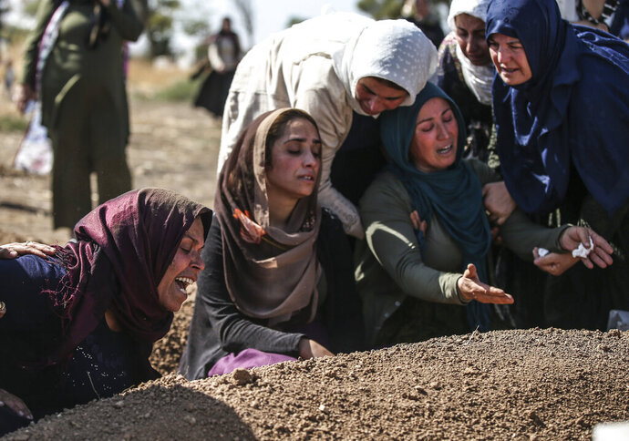 Relatives of Halil Yagmur, 64, who was killed Friday during mortar shelling from Syria, mourn over his grave at the cemetery in the town of Suruc, southeastern Turkey, at the border with Syria, Saturday, Oct. 12, 2019. Turkish forces entered Saturday the center of the Syrian border town of Ras Al-Ayn under heavy bombardment, the Turkish military and a Syrian war monitor said, as Turkey's offensive against Syrian Kurdish fighters pressed into its fourth day with little sign of relenting despite mounting international criticism. (AP Photo/Emrah Gurel)