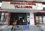 A worker sweeps up outside City Hall riddled with bullet holes, in Villa Union, Mexico, Monday, Dec. 2, 2019. The small town near the U.S.-Mexico border began cleaning up Monday even as fear persisted after 23 people were killed in a weekend gun battle between a heavily armed drug cartel assault group and security forces. (AP Photo/Eduardo Verdugo)