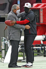 Atlanta Falcons owner Arthur Blank, left, hugs head coach Raheem Morris before an NFL football game against the Tampa Bay Buccaneers Sunday, Jan. 3, 2021, in Tampa, Fla. (AP Photo/Jason Behnken)