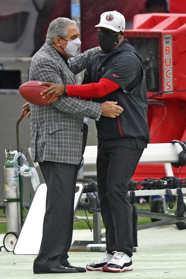 Atlanta Falcons owner Arthur Blank, left, hugs head coach Raheem Morris before an NFL football game against the Tampa Bay Buccaneers Sunday, Jan. 3, 2021, in Tampa, Fla. (AP Photo/Jason Behnken)