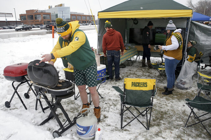 Called Zyduck, left, grills food outside of Lambeau Field before the NFC championship NFL football game between the Tampa Bay Buccaneers and Green Bay Packers in Green Bay, Wis., Sunday, Jan. 24, 2021. (AP Photo/Mike Roemer)