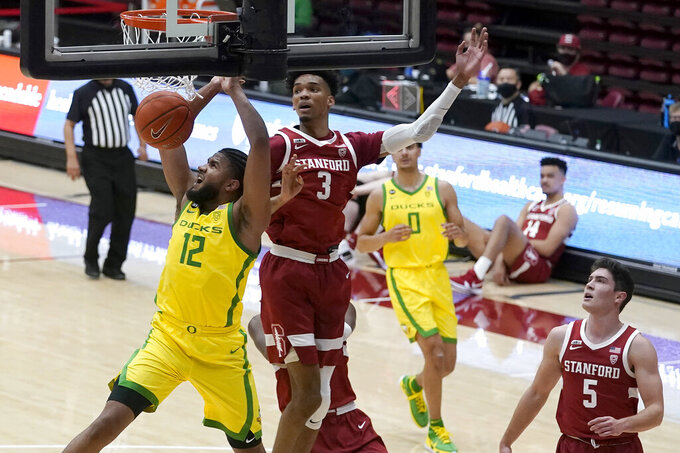 Oregon guard LJ Figueroa (12) dunks in front of Stanford forward Ziaire Williams (3) during the first half of an NCAA college basketball game in Stanford, Calif., Thursday, Feb. 25, 2021. (AP Photo/Jeff Chiu)