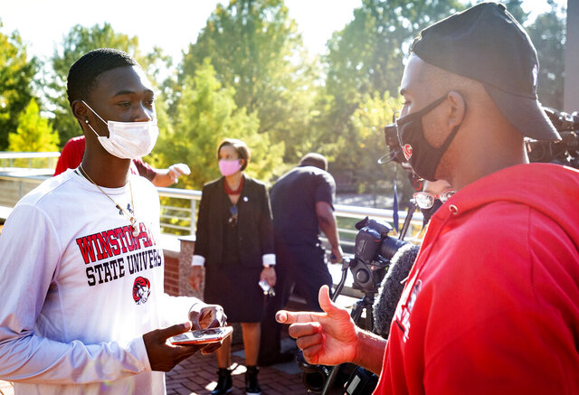 Joshua Wilson, left, a junior at Winston-Salem State University, speaks with NBA star and current Winston-Salem State University student Chris Paul about where Paul can pick up his student ID on Tuesday, Oct. 27, 2020, in Winston-Salem, N.C.  Paul led nearly 2,500 people on a march to an early-voting site at a university in North Carolina where he also takes classes.  (Andrew Dye/The Winston-Salem Journal via AP)