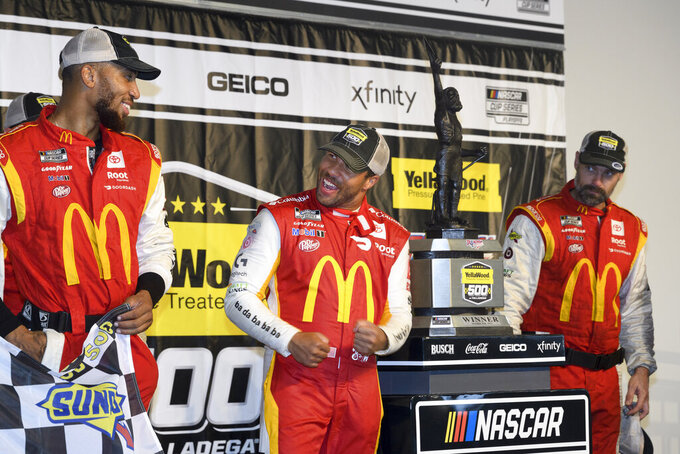 Bubba Wallace, center, celebrates with teammates as he stands next to the trophy after winning a NASCAR Cup series auto race Monday, Oct. 4, 2021, in Talladega, Ala. The race was stopped mid-race due to rain. (AP Photo/John Amis)