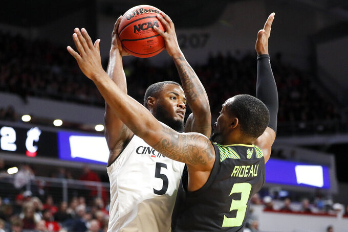 Cincinnati's Trevor Moore (5) looks to pass against South Florida's LaQuincy Rideau (3) in the first half of an NCAA college basketball game, Tuesday, Jan. 15, 2019, in Cincinnati. (AP Photo/John Minchillo)