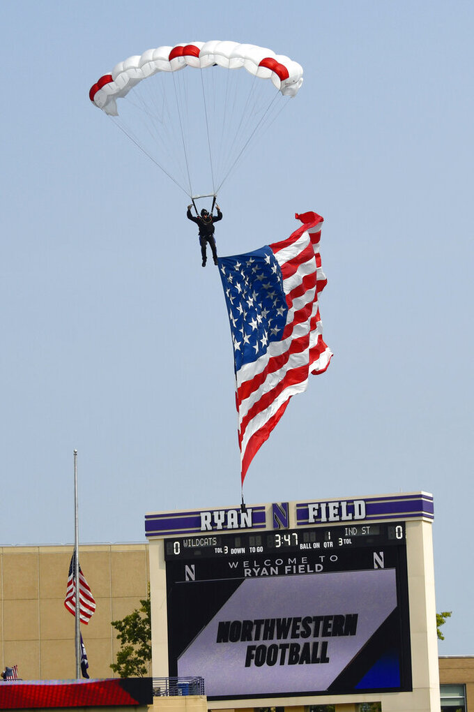 A sky diver lands on the field with an oversized United States flag prior to the start of an NCAA college football game between Northwestern and Indiana State in Evanston, Ill, Saturday, Sept. 11, 2021. (AP Photo/Matt Marton)