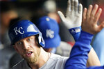 Kansas City Royals' Hunter Dozier is congratulated by teammates after hitting a solo home run during the fourth inning of the team's baseball game against the Cleveland Indians, Thursday, July 8, 2021, in Cleveland. (AP Photo/Tony Dejak)
