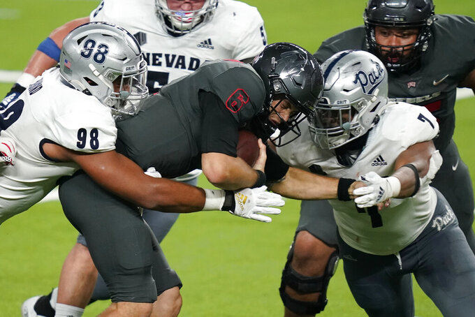 Nevada defensive end Sam Hammond, left, and defensive end Kameron Toomer (7) sack UNLV quarterback Max Gilliam (6) during the second half of an NCAA college football game Saturday, Oct. 31, 2020, in Las Vegas. (AP Photo/John Locher)