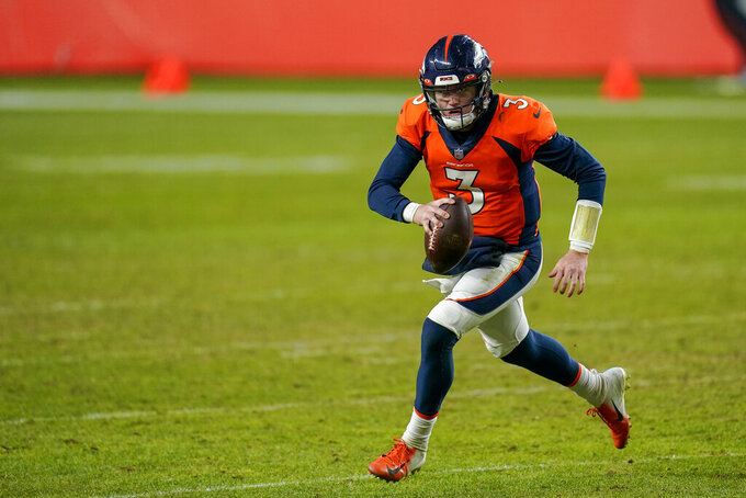 "FILE - In this Jan. 3, 2021, file photo, Denver Broncos quarterback Drew Lock scrambles against the Las Vegas Raiders during an NFL football game in Denver. ""We're really high on Drew. I like seeing Drew here every morning and when I come in he's working hard, he's trending in the right direction. As you know, he has a lot of talent. He's becoming a better pro,"" general manager George Paton said at his pre-draft news conference. ""But we're still going to look at the quarterback position."" (AP Photo/Jack Dempsey, File)"