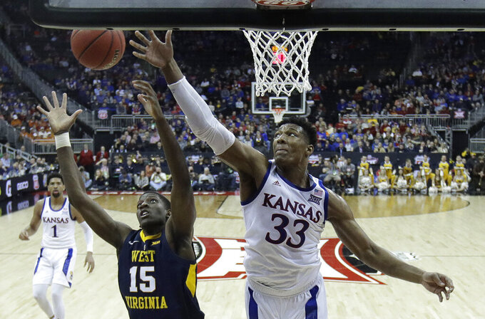 Kansas' David McCormack (33) competes for a rebound with West Virginia's Lamont West (15) during the second half of an NCAA college basketball game in the Big 12 men's tournament Friday, March 15, 2019, in Kansas City, Mo. Kansas won 88-74. (AP Photo/Charlie Riedel)