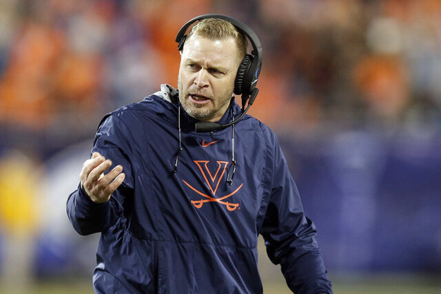 FILE - Virginia head coach Bronco Mendenhall directs his players during the second half of the Atlantic Coast Conference championship NCAA college football game against Clemson in Charlotte, N.C., Saturday, Dec. 7, 2019. One year after dynamic quarterback Bryce Perkins led Virginia to its first Coastal Division title in the Atlantic Coast Conference and a trip to the Orange Bowl, the Cavaliers will put Bronco Mendenhall's new standard to a big test this season.(AP Photo/Gerry Broome, File)