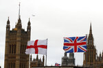 "FILE - In this file photo dated Saturday, Dec. 14, 2019, a British flag, right, and England's red cross, fly in front of the Houses of Parliament in London.  With a hefty government majority, expectations are running high for 2020 and Prime Minister Boris Johnson has pledged to ""work my socks off"" to unite the divided country. (AP Photo/Thanassis Stavrakis, FILE)"