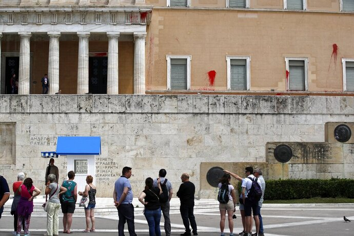 Tourists look the red paint on the wall of the Parliament building in Athens, Tuesday, May 21, 2019. A group of about 10 people threw red paint at parliament and set off a smoke bomb as Greece's Supreme Court heard an appeal against the denial of a temporary leave of absence from prison of a hunger striking extremist serving multiple life sentences for the killings of 11 people by the country's deadliest far-left group. (AP Photo/Thanassis Stavrakis)