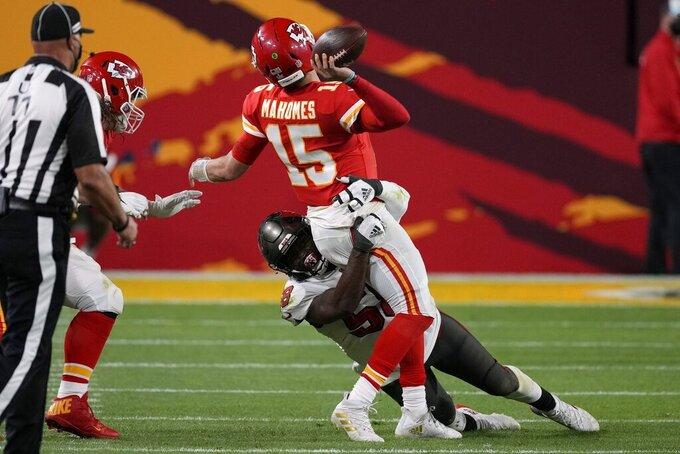 Kansas City Chiefs quarterback Patrick Mahomes (15) throws a pass while in the grasp of Tampa Bay Buccaneers outside linebacker Shaquil Barrett during the second half of the NFL Super Bowl 55 football game, Sunday, Feb. 7, 2021, in Tampa, Fla. (AP Photo/Chris O'Meara)