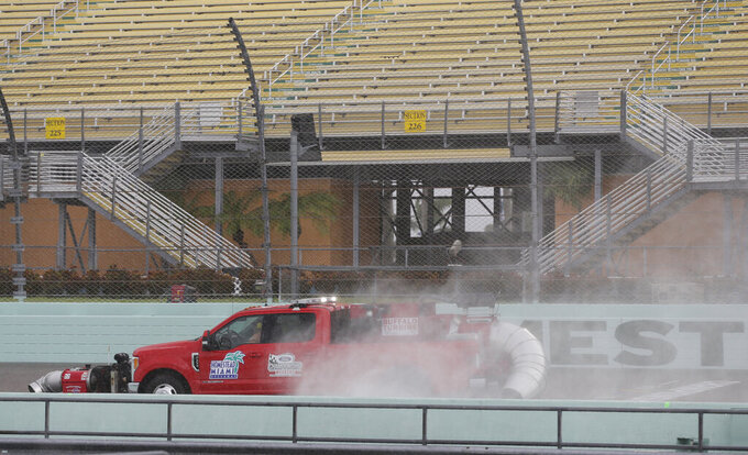 A track-drying truck drives on the front stretch during a rain delay of NASCAR auto racing activities on Friday, Nov. 15, 2019, at Homestead-Miami Speedway in Homestead, Fla. (AP Photo/Terry Renna)