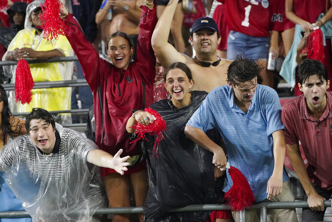 Mississippi fans brave the rain prior to an NCAA college football game against Tulane, Saturday, Sept. 18, 2021, in Oxford, Miss. A weather delay was called by officials. (AP Photo/Rogelio V. Solis)