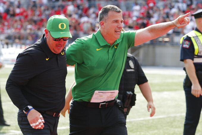 Oregon head coach Mario Cristobal, right, celebrates their 35-28 win over Ohio State after an NCAA college football game Saturday, Sept. 11, 2021, in Columbus, Ohio. (AP Photo/Jay LaPrete)