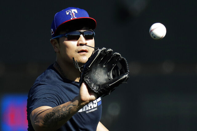 Texas Rangers' Shin-Soo Choo catches a ball during spring training baseball practice Friday, Feb. 14, 2020, in Surprise, Ariz. (AP Photo/Charlie Riedel)