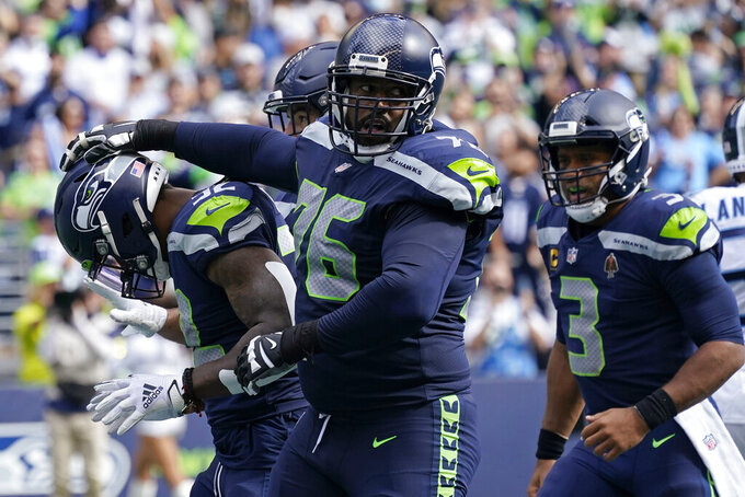 Seattle Seahawks running back Chris Carson (32), left, is greeted by offensive tackle Duane Brown (76) and quarterback Russell Wilson (3) reacts after Carson scored a touchdown against the Tennessee Titans during the first half of an NFL football game, Sunday, Sept. 19, 2021, in Seattle. (AP Photo/Elaine Thompson)