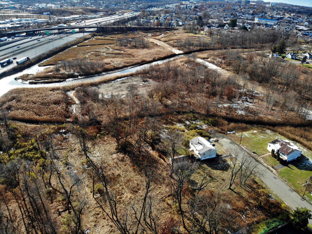 A flood-plain forest grows now where there used to be houses in the Watson Crampton neighborhood in Woodbridge, N.J., as seen from the air on Thursday, Dec. 5, 2019. The Heards Brook on the top meets the Woodbridge River on the left, which leads to the Atlantic Ocean. Homeowners here took buyouts through a program that purchases houses and demolishes them to remove people from danger and to help absorb water from rising sea levels due to climate change. (AP Photo/Ted Shaffrey)