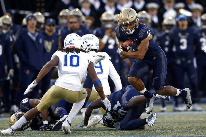 Navy slotback Malcolm Perry, right, rushes the ball against Tulsa safety Manny Bunch in the first half of an NCAA college football game, Saturday, Nov. 17, 2018, in Annapolis, Md. (AP Photo/Patrick Semansky)
