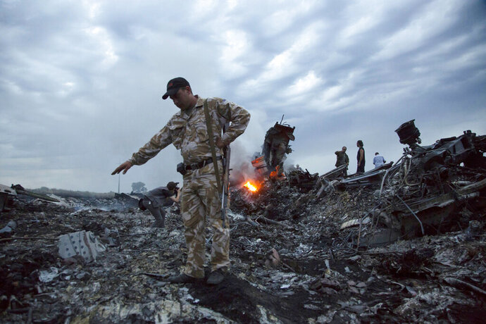 """FILE - In this July 17, 2014 file photo, people walk amongst the debris at the crash site of a passenger plane near the village of Grabovo, Ukraine. Prosecutors investigating the downing five years ago of Malaysia Airlines Flight 17 over eastern Ukraine want to speak to a man being held by Ukrainian authorities, calling him a """"person of interest"""" in their probe. (AP Photo/Dmitry Lovetsky, File)"""