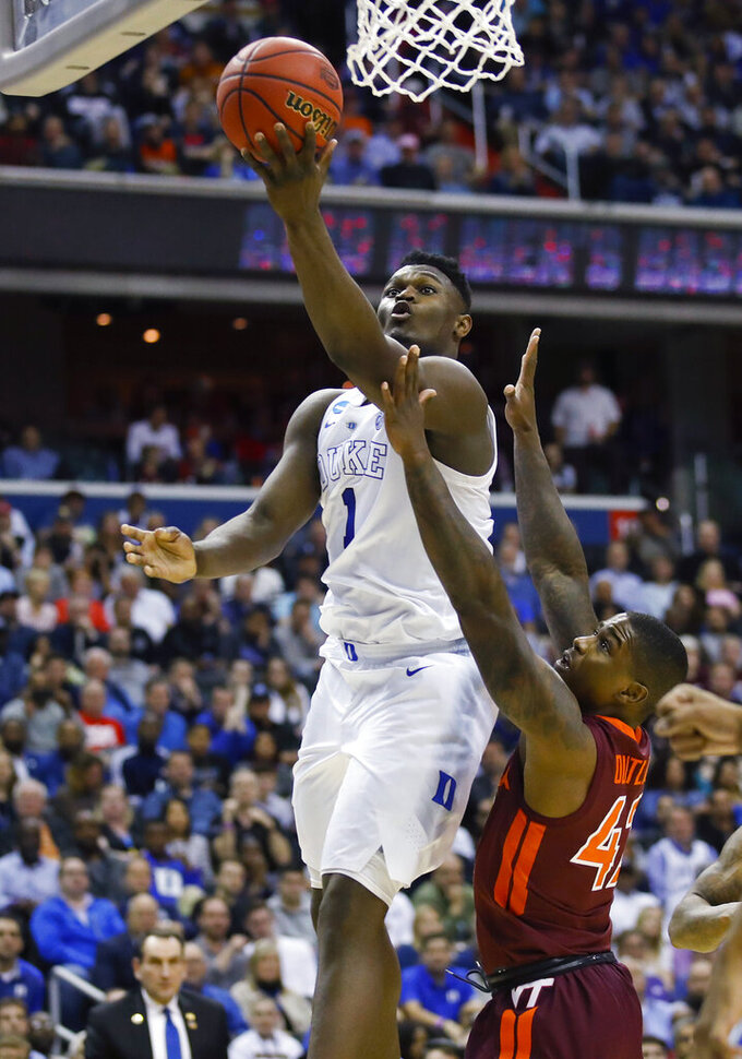Duke forward Zion Williamson (1) scores next to Virginia Tech guard Ty Outlaw (42) during the second half of an NCAA men's college basketball tournament East Region semifinal in Washington, Friday, March 29, 2019. (AP Photo/Alex Brandon)