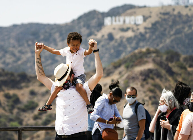 Visitors wear face masks outdoors while taking pictures of the Hollywood sign at the Griffith Observatory in Los Angeles, Monday, May 17, 2021. California is keeping its rules for wearing facemarks in place until the state more broadly lifts its pandemic restrictions on June 15. (AP Photo/Damian Dovarganes)