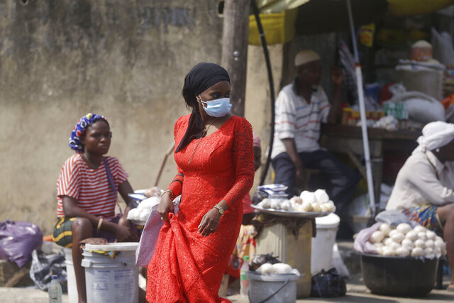 A woman wearing a face mask to protect against coronavirus, walks past people selling food at a market in Lagos, Nigeria, Thursday Dec. 24, 2020. Africa's top public health official says another new variant of the coronavirus appears to have emerged in Nigeria, but further investigation is needed. The discovery could add to new alarm in the pandemic after similar variants were announced in recent days in Britain and South Africa and sparked the swift return of travel restrictions. (AP Photo/Sunday Alamba)