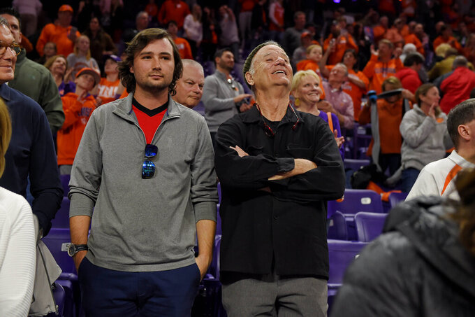 Actor Bill Murray, right, and his son Jackson William Murray, left, watch during the second half of an NCAA college basketball game between Clemson and Louisville, Saturday, Feb. 15, 2020, in Clemson, S.C. (AP Photo/Richard Shiro)