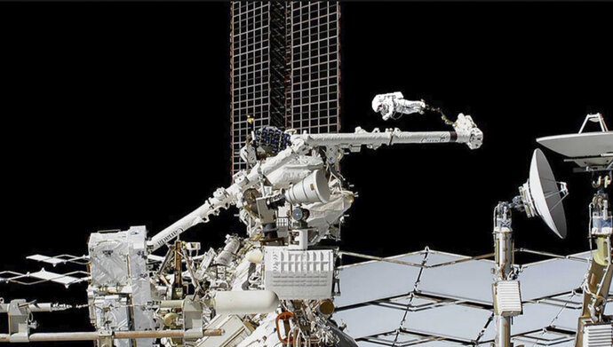 In this photo provided by NASA, astronaut Luca Parmitano is guided on the Canadarm2 robotic arm toward the work site on the Alpha Magnetic Spectrometer, the space station's cosmic particle detector at the International Space Station, Friday, Nov. 22, 2019. Spacewalking astronauts ventured out for the second week in a row Friday to repair a cosmic ray detector, this time actually cutting into the $2 billion instrument. (NASA via AP)