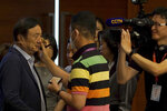 Huawei founder Ren Zhengfei, left, gets make up on his face before attending a roundtable at the telecom giant's headquarters in Shenzhen in southern China on Monday, June 17, 2019. Huawei's founder has likened his company to a badly damaged plane and says revenues will be $30 billion less than forecast over the next two years. (AP Photo/Dake Kang)