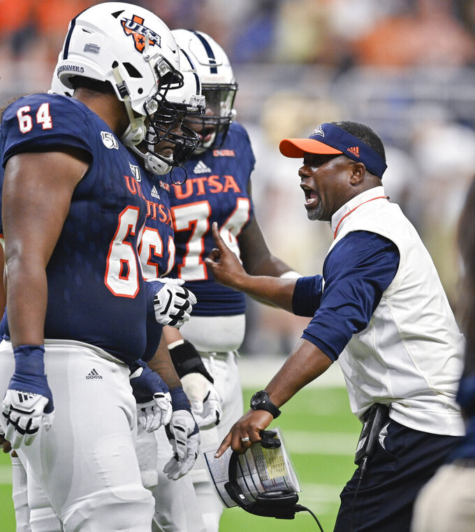 UTSA head coach Frank Wilson, right, talks to players, from left to right, Josh Dunlop Kevin Davis and Spencer Burford during the first half of an NCAA college football game against Army, Saturday, Sept. 14, 2019 in San Antonio. (AP Photo/Darren Abate)