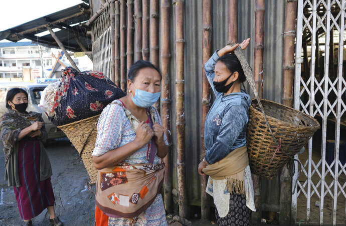 Naga women wear masks as a precaution against the coronavirus and walk past closed shops early morning in Kohima, capital of the northeastern Indian state of Nagaland, Tuesday, June 30, 2020. Several Indian states have reimposed partial or full lockdowns to stem the spread of the coronavirus. (AP Photo/Yirmiyan Arthur)