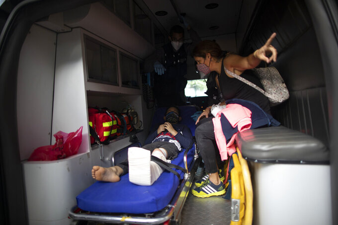 A boy who was involved in a motorcycle accident is transported to the hospital by Angels of the Road volunteer paramedics in their only ambulance in Caracas, Venezuela, Thursday, Feb. 4, 2021. The volunteer corps relies on donated medical supplies and funding from international organizations to provide much-needed emergency services, operating entirely independent of the government. (AP Photo/Ariana Cubillos)