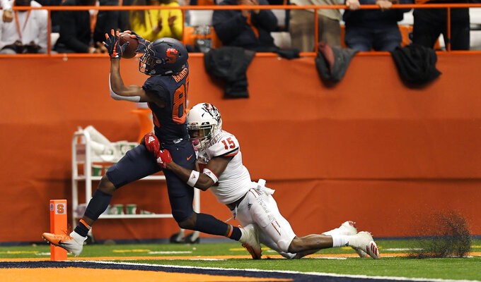 Syracuse wide receiver Taj Harris, left, drags North Carolina State cornerback Chris Ingram across the goal line for an Orange touchdown during the second half of an NCAA college football game in Syracuse, N.Y., Saturday, Oct. 27, 2018. (AP Photo/Adrian Kraus)