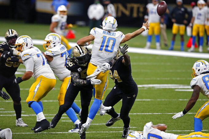 Los Angeles Chargers quarterback Justin Herbert (10) passes under pressure from New Orleans Saints outside linebacker Demario Davis (56) and defensive end Cameron Jordan (94) in the second half of an NFL football game in New Orleans, Monday, Oct. 12, 2020. (AP Photo/Butch Dill)